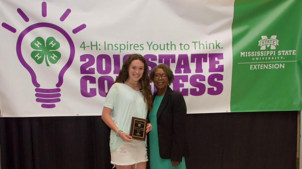A teenage girl holding a plaque stands next to an older woman in front of a purple, green, and white 4-H poster.