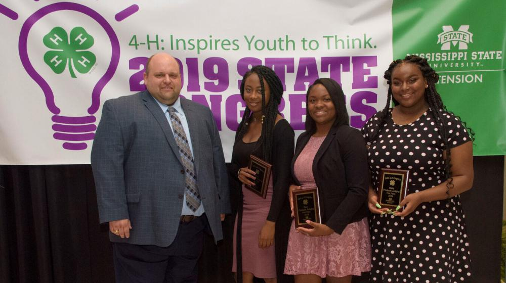 Three teenage girls holding plaques stand next to a man in front of a purple, green, and white 4-H poster.