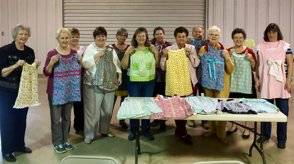 a group of homemaker volunteers with the dresses they made.