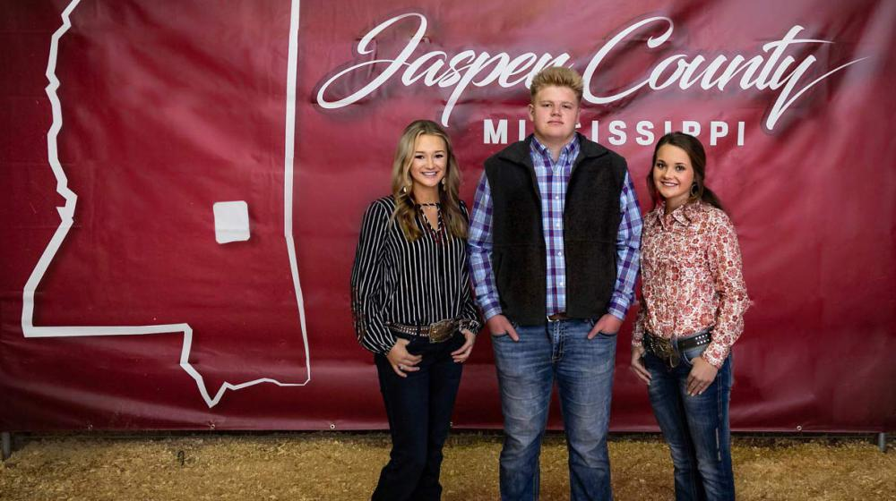 """Three young people standing in front of a red banner that says """"Jasper County""""."""