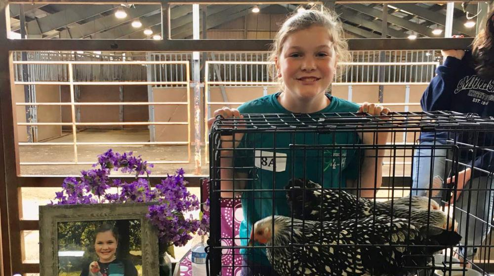 Girl behind a cage of chickens.