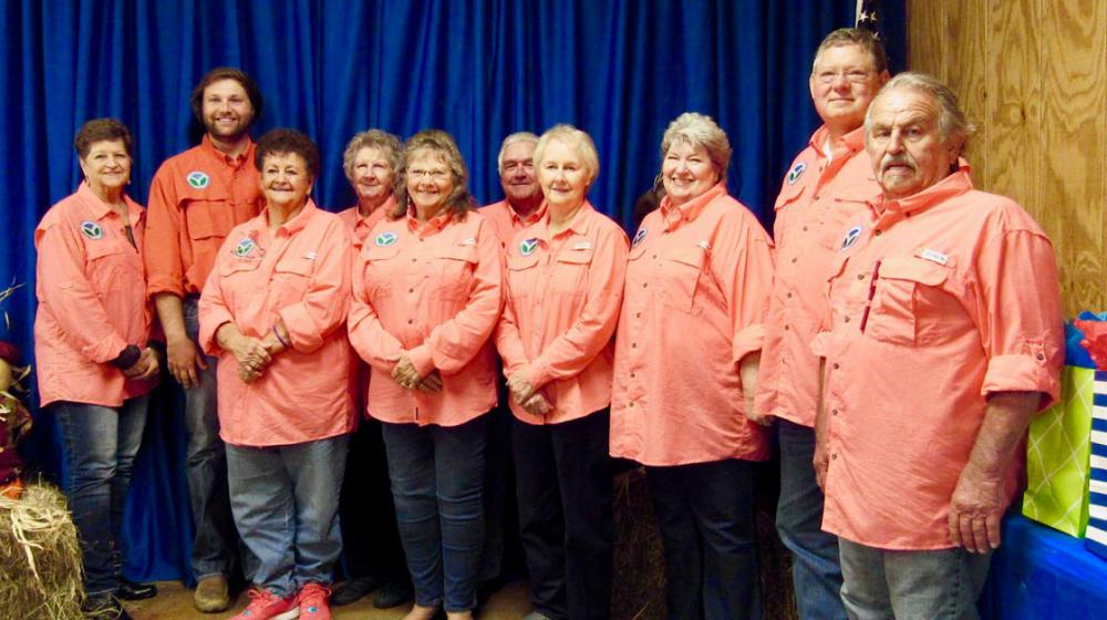 Ten adults standing in a row for a photo.