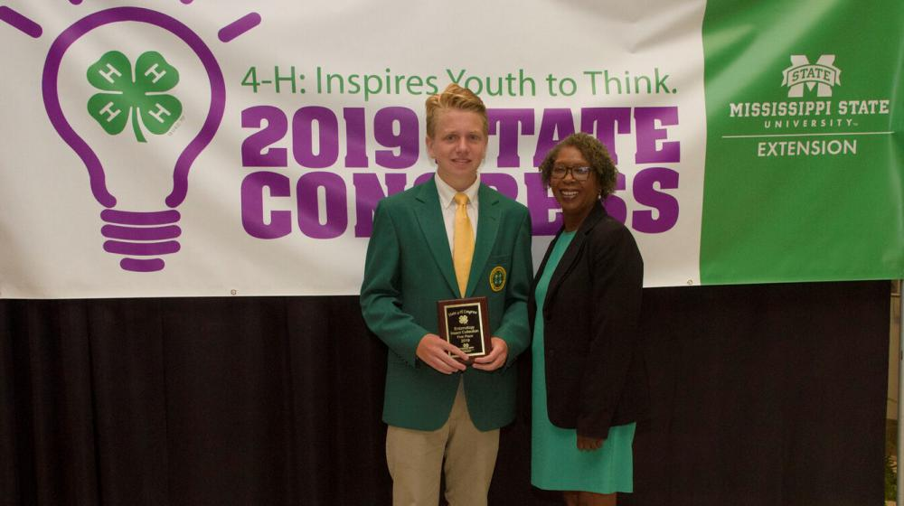 A teenage boy wearing a green blazer and holding a plaque stands next to an older woman in front of a purple, green, and white 4-H poster.