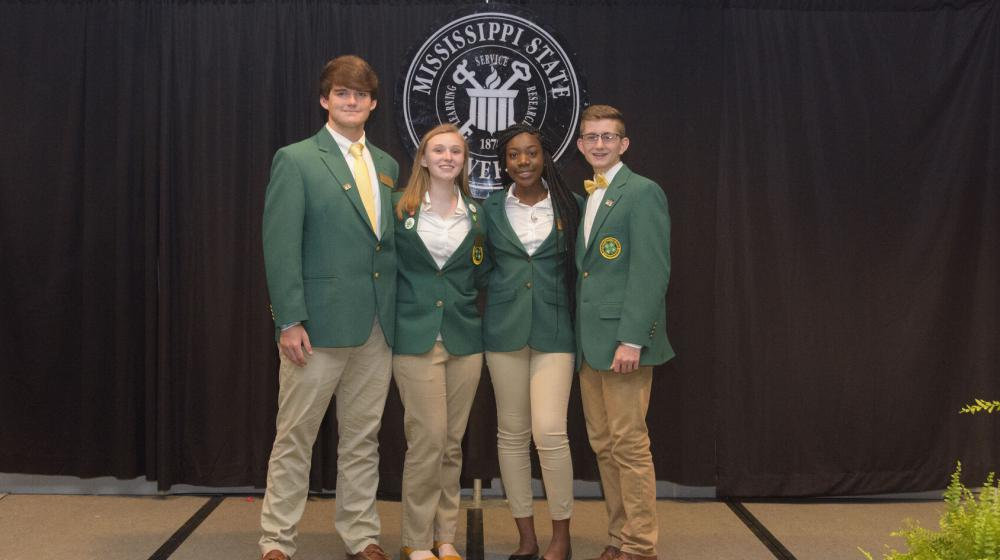 Four teenagers wearing green blazers stand in front of a black curtain.