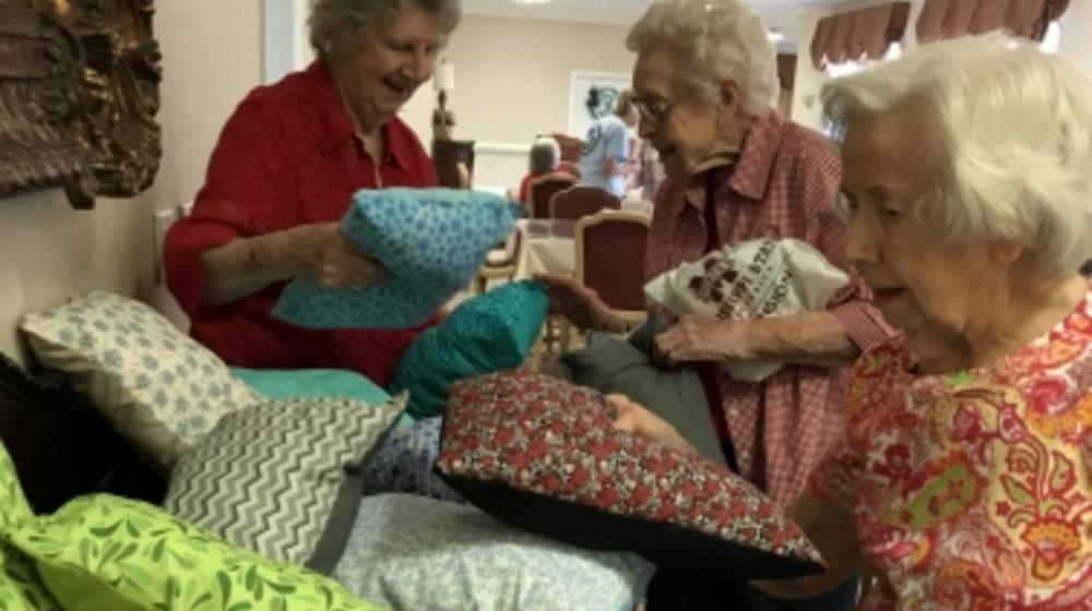 three ladies with colorful pillows that they made.