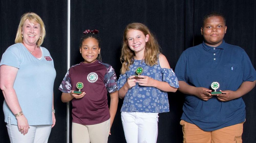 Three young kids holding small green 4-H trophies smile next to an older woman wearing a maroon name tag.