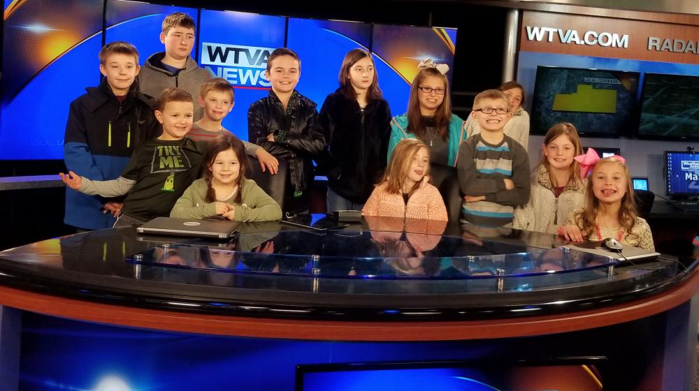 "Thirteen young kids stand behind a table with ""WTVA News"" on the screens in front and behind them."