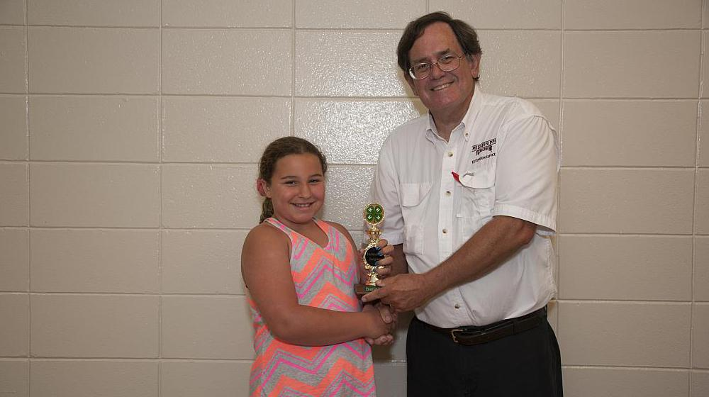 A 4-H member receiving an award from a Mississippi State University Extension Service agent.