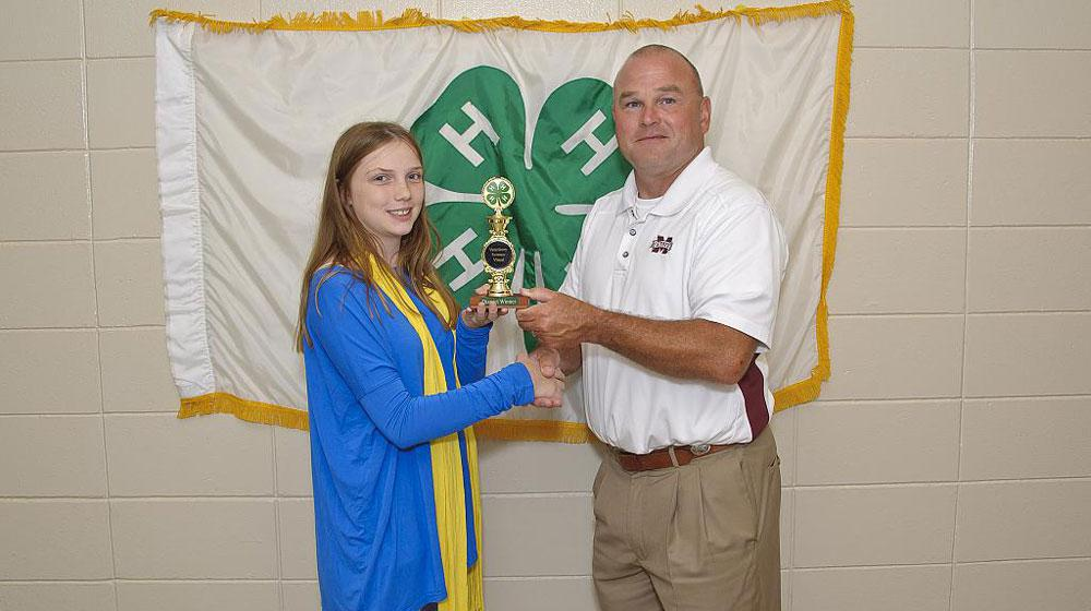 girl with 4-H award.