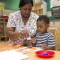 Penny Lee, a teacher at Global Connection Learning Center in Jackson, helps 2-year-old Jacob Sargent with an art project. Early care and education providers like Lee will be honored on Provider Appreciation Day May 10. (Photo by MSU School of Human Sciences/Alicia Barnes)