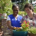 Two women smile as they enjoy colorful potted ornamental plants.