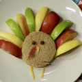A round peanut butter and jelly sandwich sits on a white plate. It is decorated to look like a turkey, with green, red, and yellow apple slices for feathers, chocolate chips for eyes, cheese for a nose and legs, and a small bit of bacon for a wattle. The plate sits on a multicolored floral placemat.