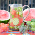 A pitcher of iced, flavored water sits in the center of a halved watermelon, bowls of cubed watermelon, limes and jalapenos.