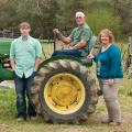 An older man, a woman, and a teenage boy around a green tractor.