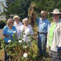 Six Master Gardeners pose in a rose garden after weeding it