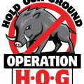 :Black, white, and red logo showing a stylized wild hog with a red circle and a diagonal line across. Text reads Hold Our Ground Operation H.O.G.