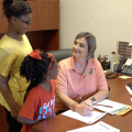 Woman filling out paper work with two children.