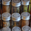 Rows of spices in clear jars with silver tops.