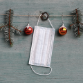 A white mask hanging on Christmas garland.