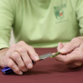 A person wearing a green shirt scraping a stem with a razor bade.
