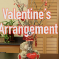 This Valentine's arrangement has a stuffed bear and a red heart hugging an arrangement of twigs with candy attached using red ribbon.