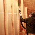 A man fits insulation around water pipes in an unfinished attic of a home.