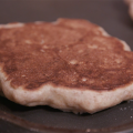 A close-up of a golden brown whole-grain pancake on a nonstick griddle, with parts of two other pancakes blurred in the background.