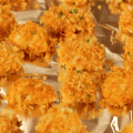 Chicken nuggets coated in golden brown panko breadcrumbs on an aluminum-foil lined baking sheet.