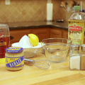 The ingredients and equipment to make honey lemon vinaigrette are displayed on a kitchen table, including honey, olive oil, half of a lemon, salt, pepper, minced garlic, a small glass bowl, a stainless steel whisk, and a citrus juicer.