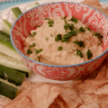 A plate with zuchinni, freshly baked chips, and a bowl of hummus in the center