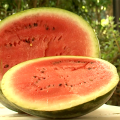 A sliced, ripe watermelon sits on a table outdoors.