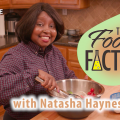 Natasha Haynes, an African American female wearing a plaid dress shirt stands in a kitchen and uses tongs to mix food ingredients in a stainless steel bowl. A tall bottle of olive oil is on the table.