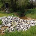 A pile of large gray rocks stretches across a ditch in a country setting.