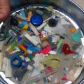 Looking down on a round pan with various small pieces of plastic.