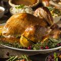 A roasted turkey and side dishes fill a table set for a meal.