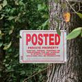 A private property sign is nailed to a tree with vegetation in the background.