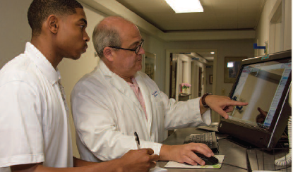 An image of a RMS scholar viewing an x-ray with a physician.
