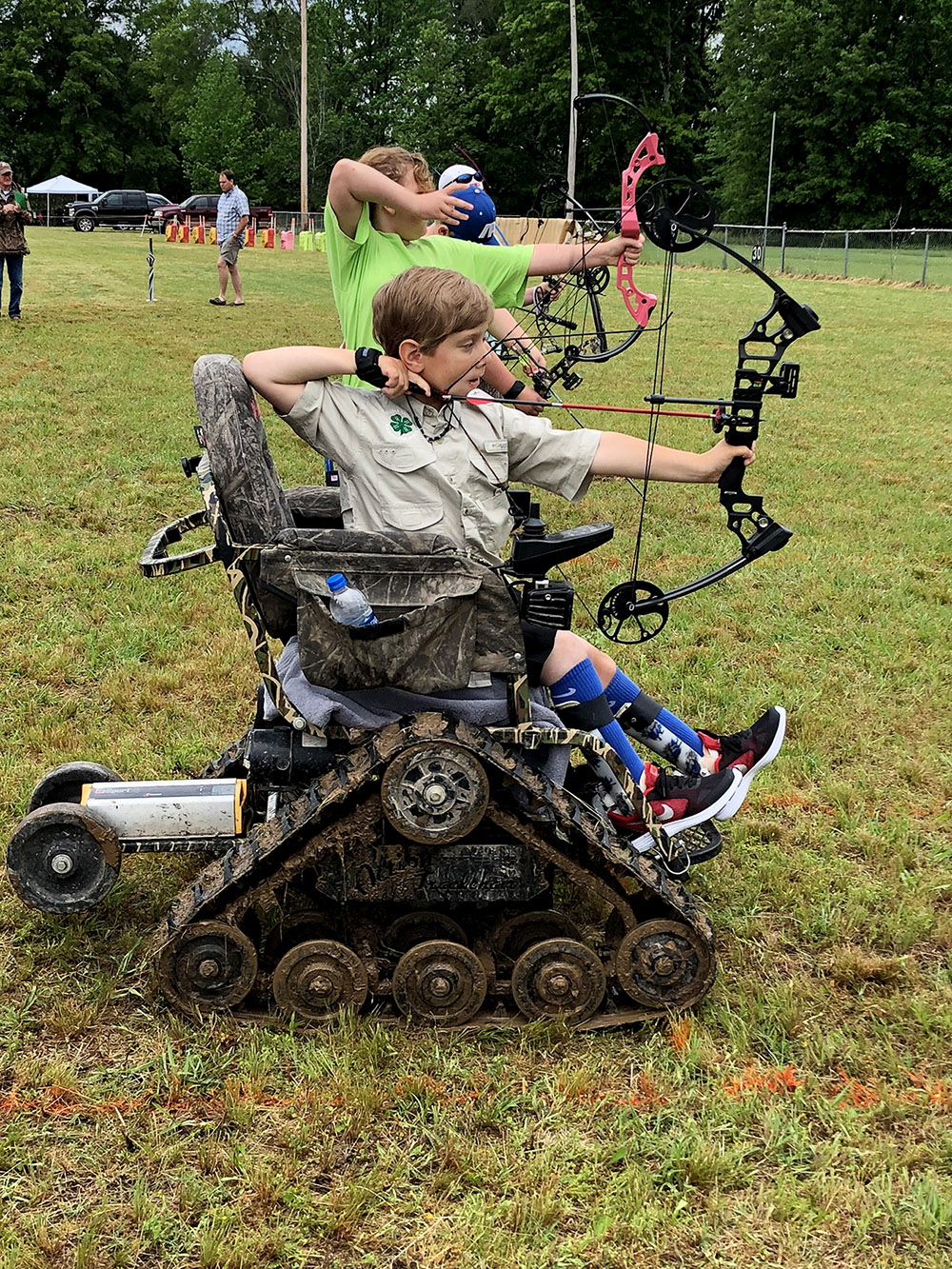 A teenager aiming his bow and arrow from his wheelchair.