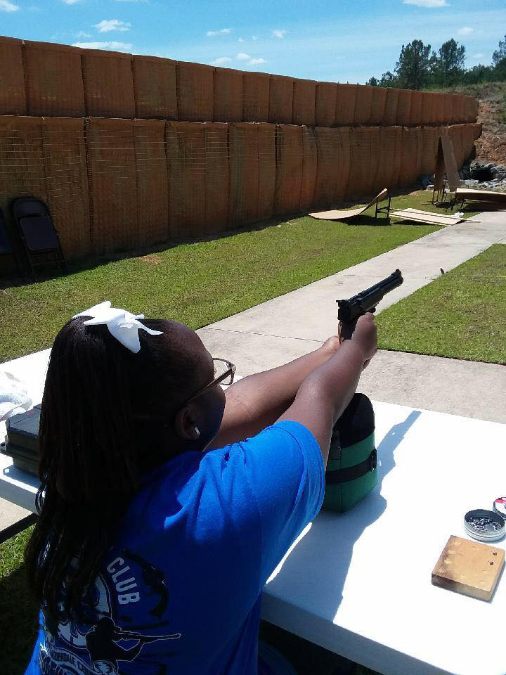 Girl aims and shoots pistol at target during competition.