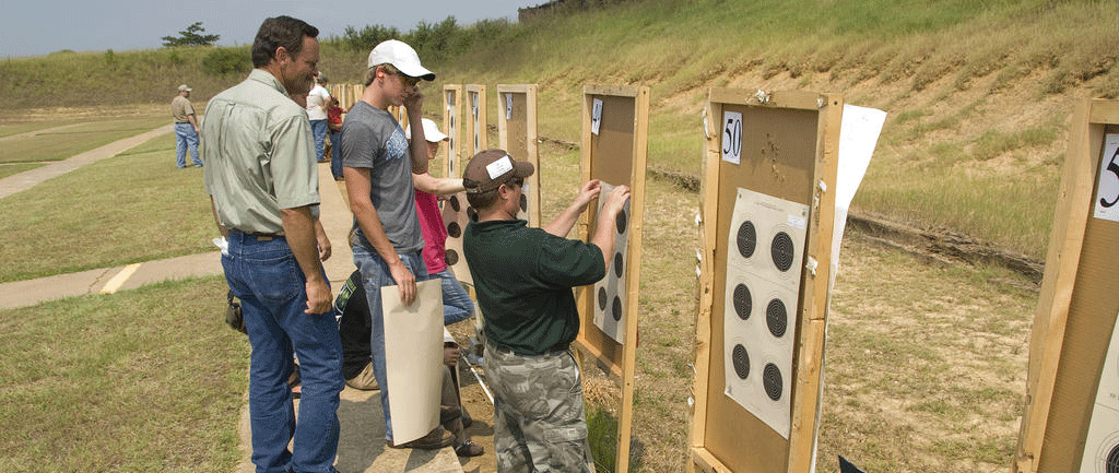 Two men watching one other man set up a target sheet with six targets on a board with a number labeled 49 in the top left corner and an identical board and target is to the right of them but labeled with 50 in the top left corner.