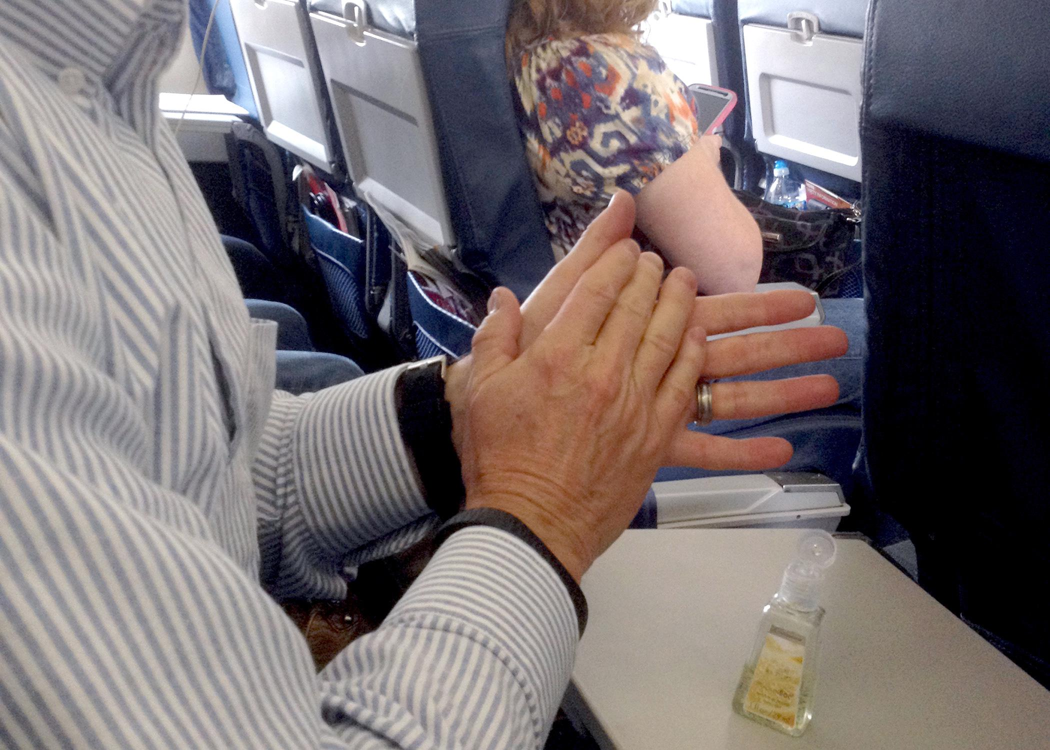 man washing hands with alcohol-based rub seated in airplane.