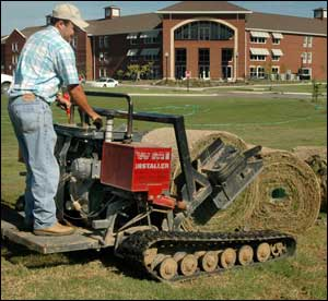 Steve Hughes lays down sod near one of Mississippi State University's new residence halls.
