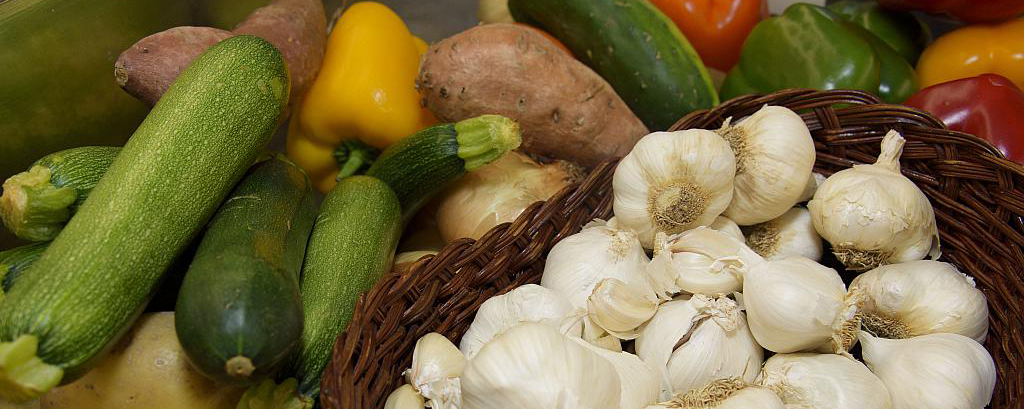 This is an image of different foods, potato, garlic, peppers, and zuchinni