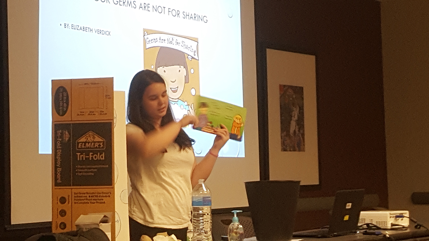 Natalie Gill is showing a book that you could read to preschoolers to teach about handwashing during her health visual