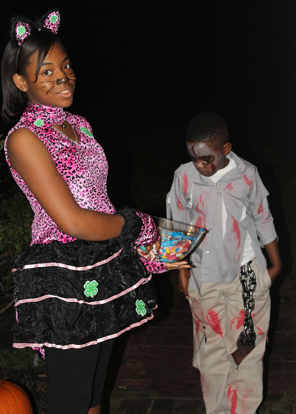 Two children dressed in costume with a bowl of candy while trick or treating.