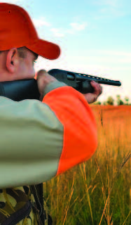 A hunter wearing orange cap and orange on his sleeves, practices safety while aiming a rifle.