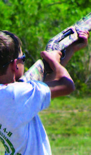 A Shooting Sports participant aims a camouflage shotgun.