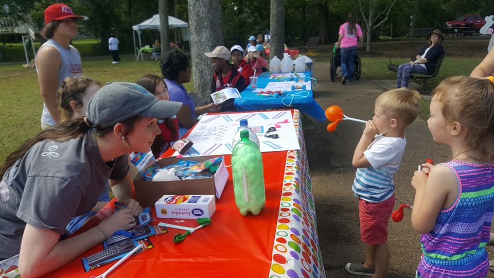"Dakota Edwards looks on as Senatobia Five Star City Fest participants learn about ""lung capacity"" at the Healthy Lung Kids station."