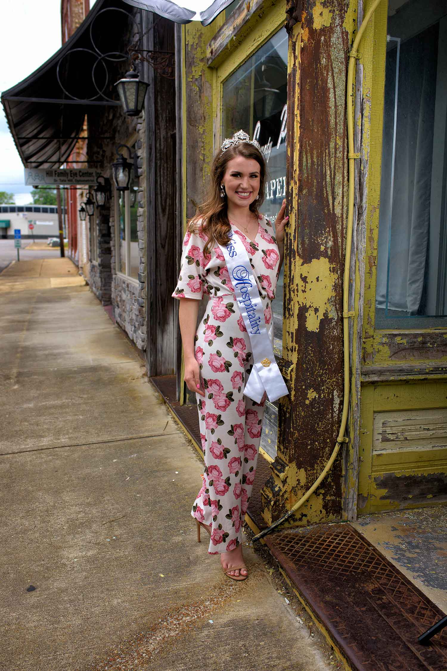 "A young woman with brown hair and a silver crown wears a white jumpsuit with pink roses and a white sash embroidered with the words ""Miss Hospitality."" She stands with her hand resting on a yellow, chipped wooden storefront."