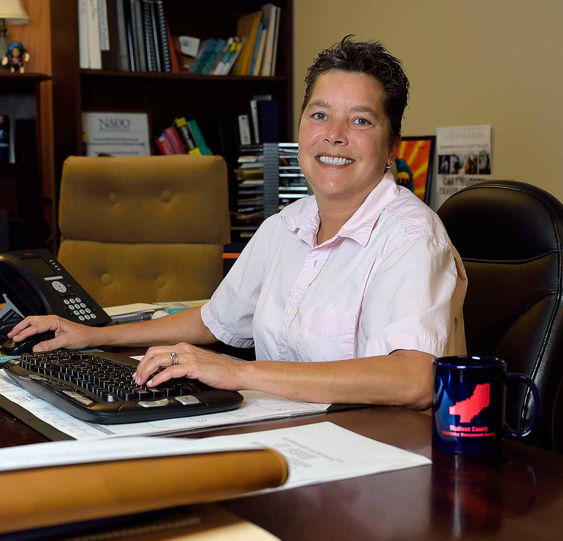 A woman with short hair and a collared, light pink shirt sits at her desk smiling. Her desk has papers and notebooks on it, along with a coffee mug, keyboard, and office phone.